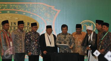 Wapres Jusuf Kalla disaksikan Ketua PBNU Said Aqil Siroj (ketiga kanan) usai menandatangani kartu NU Care pada acara peluncuran di Jakarta, Kamis (25/2). NU Care memberikan kemudahaan pada masyarakat untuk berzakat dengan tertib. (Liputan6.com/JohanTallo)