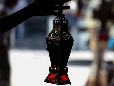 "Pria Mesir memegang lentera tradisional yang dikenal dalam bahasa Arab sebagai ""Fanous"" yang dijual selama bulan suci Ramadan di Sayeda Zainab, Kairo, 19 April 2020.  Menjelang Ramadan 1441 H, warga Mesir mulai berburu lentera warna-warni di tengah pandemi corona Covid-19. (Mohamed el-Shahed/AFP)"