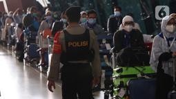 Aparat kepolisian mengamati rombongan jemaah umrah saat tiba di Bandara Soekarno Hatta, Tangerang, Selasa (29/12/2020). Rombongan jemaah umrah yang baru tiba di Indonesia tersebut diarahkan untuk melakukan karantina di tempat yang telah disediakan oleh pemerintah. (Liputan6.com/Angga Yuniar)