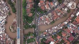 Foto udara suasana Sungai Ciliwung yang diapit pemukiman padat penduduk di kawasan Manggarai, Jakarta, Selasa (7/1/2020). Pemprov DKI Jakarta akan membebaskan 118 bidang lahan untuk proyek normalisasi Sungai Ciliwung pada tahun 2020 yang tersebar di empat kelurahan. (Liputan6.com/Immanuel Antonius)
