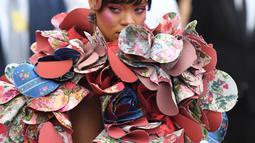 Penampilan Rihanna pada acara penggalangan dana Met Gala 2017 di Metropolitan Museum of Art, New York, Senin (1/5). Rihanna mengenakan busana dengan aksen bunga di sekelilingnya, yang bahannya saling bertumpuk seperti kelopak bunga. (ANGELA WEISS/AFP)