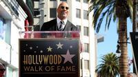 Aktor Dwayne Johnson menyampaikan pidatonya selama upacara penganugerahaan bintang Hollywood Walk of Fame  di Los Angeles, Jumat (13/12). (Photo by Willy Sanjuan/Invision/AP)