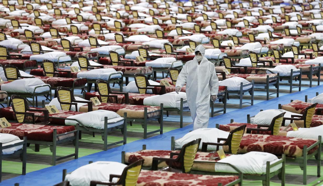 Petugas berpakaian pelindung berjalan melewati deretan tempat tidur di rumah sakit sementara khusus pasien virus corona COVID-19 di Teheran, Iran, Kamis (26/3/2020). Rumah sakit sementara yang dibangun di pusat pameran internasional ini memiliki 2.000 tempat tidur. (AP Photo/Ebrahim Noroozi)