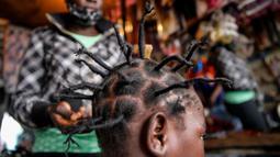 Gettrueth Ambio (12) rambutnya ditata dengan model yang terinsprasi dari corona Covid-19 oleh Mama Brayo Beauty Salon di daerah kumuh Kibera, Kenya, 3 Mei 2020. Corona telah menghidupkan kembali gaya rambut di Afrika Timur yang memiliki lonjakan kepang bentuk khas virus. (AP/Brian Inganga, File)