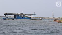 Sebuah kapal terdampar di di kawasan Pulau G Reklamasi, Muara Angke, Jakarta Utara, Kamis (31/10/2019). Bagi nelayan yang sudah biasa berlayar dari dermaga Muara Angke mereka langsung menghindari kawasan Pulau G tersebut. (Liputan6.com/Herman Zakharia)