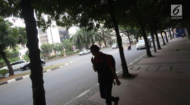 Pejalan kaki melintas di Jalan Sudirman, Jakarta, Selasa (19/9). Terkait pembangunan trotoar, Sekda DKI Saefullah mengatakan ribuan pohon akan dipindahkan ke lokasi yang merupakan aset Pemprov DKI, seperti Taman BMW. (Liputan6.com/Immanuel Antonius)