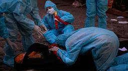 Kerabat dengan mengenakan alat pelindung diri menangis di dekat tubuh saat kremasi seseorang yang meninggal karena virus corona COVID-19 di Gauhati, India pada 28 September 2020. (AP Photo/Anupam Nath)