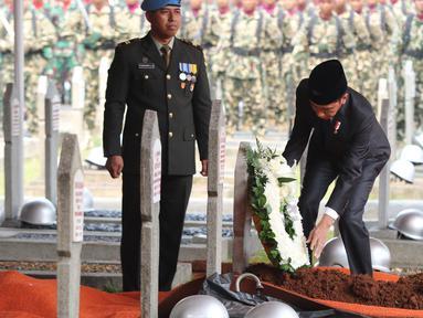 Presiden Joko Widodo meletakan karangan bunga di makam Presiden ke-3 RI Bacharuddin Jusuf Habibie di TMP Kalibata, Jakarta, Kamis (12/9/2019). Habibie wafat pada Rabu (11/9/2019) dalam usia 83 tahun saat menjalani perawatan di RSPAD Gatot Soebroto. (Liputan6.com/Herman Zakharia)