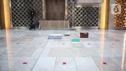 Petugas memasang tanda silang antar saf di Masjid Istiqlal, Jakarta Pusat, Selasa (2/6/2020). Masjid Istiqlal merupakan salah satu sarana ibadah yang dipersiapkan menerapkan prosedur standar new normal atau kenormalan baru. (Liputan6.com/Faizal Fanani)