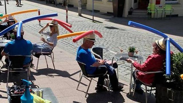 Penggunaan topi balon untuk menjaga jarak antar pengunjung di salah satu restoran di Berlin, Jerman.