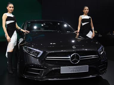 "Dua model berpose di samping Mercedes Benz CLS 53 2019 selama Thailand International Motor Expo di Bangkok (29/11). Thailand International Motor Expo bertema ""Enjoy Driving! Before Driverless Era"".  (AFP Photo/Lillian Suwanrumpha)"