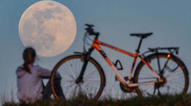 Pengendara sepeda berhenti untuk menyaksikan supermoon di Sieversdorf, Jerman, Selasa (7/4/2020). Fenomena dimana bulan berada pada titik terdekat dengan bumi ini merupakan penampakan supermoon terbesar di tahun 2020. (Patrick Pleul /dpa/AFP)