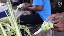 Pedagang membuat kulit ketupat siap jual di Pasar Kemiri Muka, Depok, Jawa Barat, Selasa (12/6). Menjelang Lebaran, pedagang kulit ketupat mengaku kebanjiran pembeli. (Liputan6.com/Herman Zakharia)