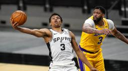 Pebasket Los Angeles Lakers, Anthony Davis, berebut bola dengan pebasket San Antonio Spurs, Keldon Johnson, pada laga NBA di AT&T Center, Kamis (31/12/2020). LA Lakers menang dengan skor 121-107. (AP/Eric Gay)