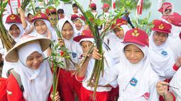 Siswa-siswi  SD Nasima Semarang memegang tanaman mangrove saat menanamnya di Teluk Pantai Mangunharjo, Jumat (18/1). Sebanyak 2500 bibit mangrove ditanam untuk melindungi pantai dan tebing sungai dari proses erosi atau abrasi. (Liputan6.com/Gholib)