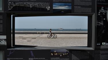 Seorang wanita mengendarai sepeda di sepanjang tepi pantai Thessaloniki, Yunani utara (23/6/2021).  Yunani bersiap menghadapi gelombang panas pertama musim panas, mendorong suhu siang hari ke wilayah 40+ Celcius di banyak bagian negara. (AFP/Sakis Mitrolidis)