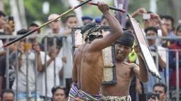 Dua pepadu (petarung) melakukan duel dalam kesenian tradisional peresean di Praya, Lombok Tengah, Selasa (19/2). Mereka bersenjatakan tongkat rotan (penjalin) dan berperisai kulit kerbau yang tebal dan keras (perisai disebut ende). (MOH EL SASAKY/AFP)