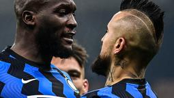 Gelandang Inter Milan, Arturo Vidal (kanan) berselebrasi dengan Romelu Lukaku usai mencetak gol ke gawang Juventus menit ke-12 pada pertandingan Liga Italia di stadion San Siro, Milan, Senin (18/1/2021). Dengan kemenangan ini, Inter menempel AC Milan di puncak klasemen. (AFP/Miguel Medina)