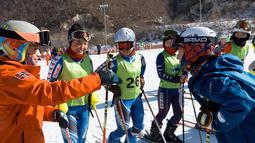 Pemain ski Korea Selatan dan Korea Utara bebincang saat mengikuti latihan di resor ski Masik Pass di Korea Utara, (1/2). Para pemain ski dan skater Korut tiba di bandara Korsel untuk berpartisipasi dalam Olimpiade Musim Dingin. (Korea Pool/Yonhap via AP)