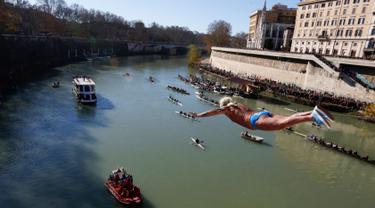 Maurizio Palmulli dari Italia melakukan terjun bebas ke sungai Tiber dari Jembatan Cavour di Roma, Selasa (1/1). Tradisi melompat dari jembatan setinggi 18 meter  dan menyelam ke sungai tersebut sebagai bentuk perayaan tahun baru. (AP/Riccardo De Luca)