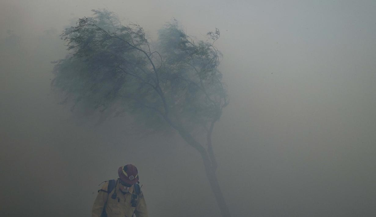 Seorang petugas pemadam kebakaran melawan angin kencang saat asap tebal dari Kebakaran Silverado memenuhi udara di Irvine, California, Senin (26/10/2020). Api yang bergerak cepat memaksa perintah evakuasi untuk 60.000 orang di California Selatan (AP Photo/Jae C. Hong)