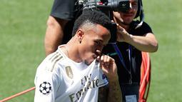 Bek Real Madrid, Eder Militao mencium logo jersey klub barunya selama pengenal dirinya di stadion Santiago Bernabeu di Madrid, Spanyol (10/7/2019). Pemain berusia 21 tahun ini menandatangani kontrak selama enam tahun di Real Madrid. (AP Photo/Manu Fernandez)