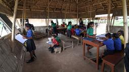 Gambar pada 20 Mei 2019, siswa India mengikuti kegiatan belajar mengajar di sekolah Forum Akshar di desa Pamohi, Guwahati. Sekolah ini mengambil pendekatan baru untuk mengatasi momok sampah plastik dengan menjadikannya sebagai syarat pengganti biaya sekolah. (Biju BORO/AFP)