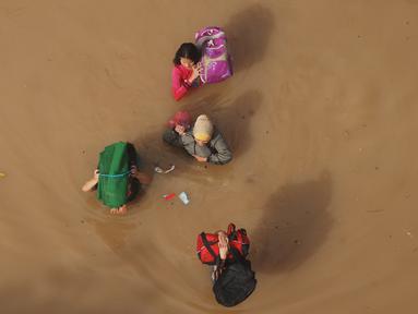 Warga menembus banjir yang merendam kabupaten Bandung, Jawa Barat, Minggu (13/3). Kawasan Bandung Selatan kembali dilanda banjir akibat luapan Sungai Citarum dan membuat lebih dari 3000 jiwa mengungsi. (Timur Matahari/AFP)