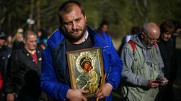 Seorang pria membawa simbol Perawan Maria selama prosesi keagamaan tahunan di Biara Bachkovo, Bulgaria (9/4). Prosesi keagamaan yang diadakan tiap tahun ini dilaksanakan pada hari kedua Paskah Ortodoks. (AFP Photo/Nikolay Doychinov)