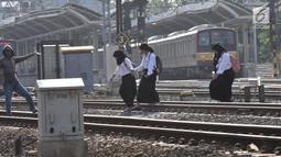 Sejumlah pelajar menyeberangi perlintasan rel kereta api di kawasan Pisangan Baru, Jakarta, Selasa (10/9/2019). Mereka nekat menantang maut menyeberangi rel di dekat stasiun Jatinegara tersebut lantaran tidak adanya akses jembatan penyeberangan orang (JPO). (merdeka.com/Iqbal Nugroho)