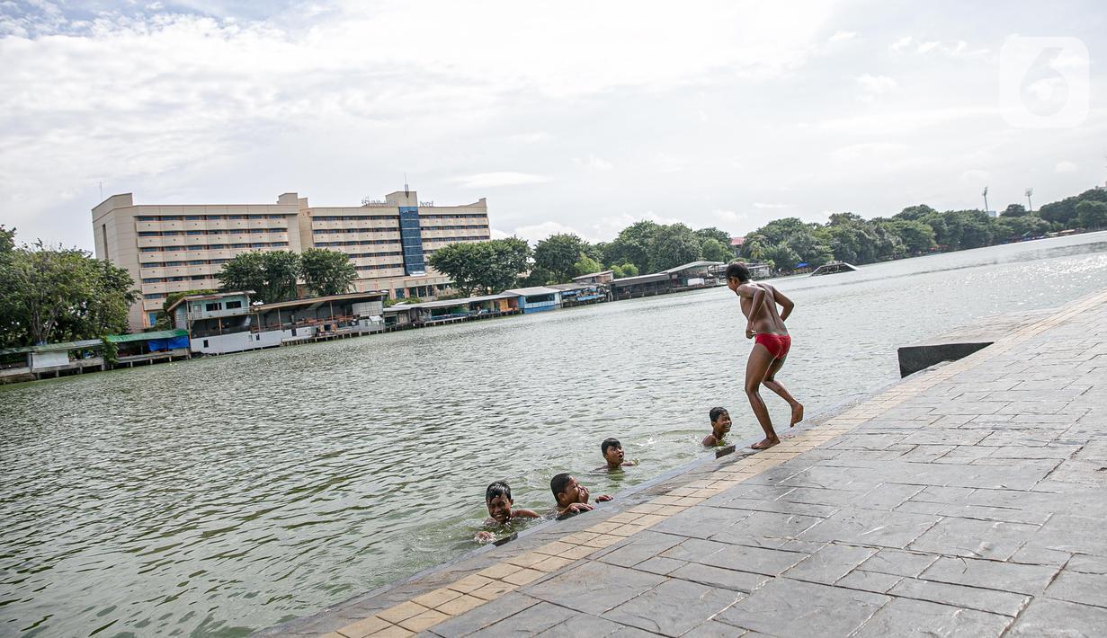 Sejumlah anak berenang di Danau Sunter, Jakarta, Selasa (2/2/2021). Minimnya lahan bermain anak membuat mereka memanfaatkan tempat yang tidak semestinya untuk bermain karena adanya risiko hanyut dan tenggelam bila tidak mampu untuk berenang. (Liputan6.com/Faizal Fanani)