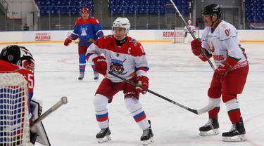 Presiden Rusia Vladimir Putin (kiri) dan Presiden Belarus Alexander Lukashenko (kanan) ikut serta dalam pertandingan hoki es di Shayba Arena, Resor Laut Hitam Sochi, Rusia, (15/2). (Sergei Chirikov / Pool / AFP)