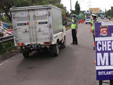 Petugas kepolisian melakukan pengecekan terhadap kendaraan yang keluar Tol Merak, Banten, Senin (18/5/2020). Pemeriksaan (check point) tersebut terkait larangan mudik guna penyekatan atau memeriksa kemungkinan pemudik yang akan keluar dari wilayah Jabodetabek. (Liputan6.com/Angga Yuniar)