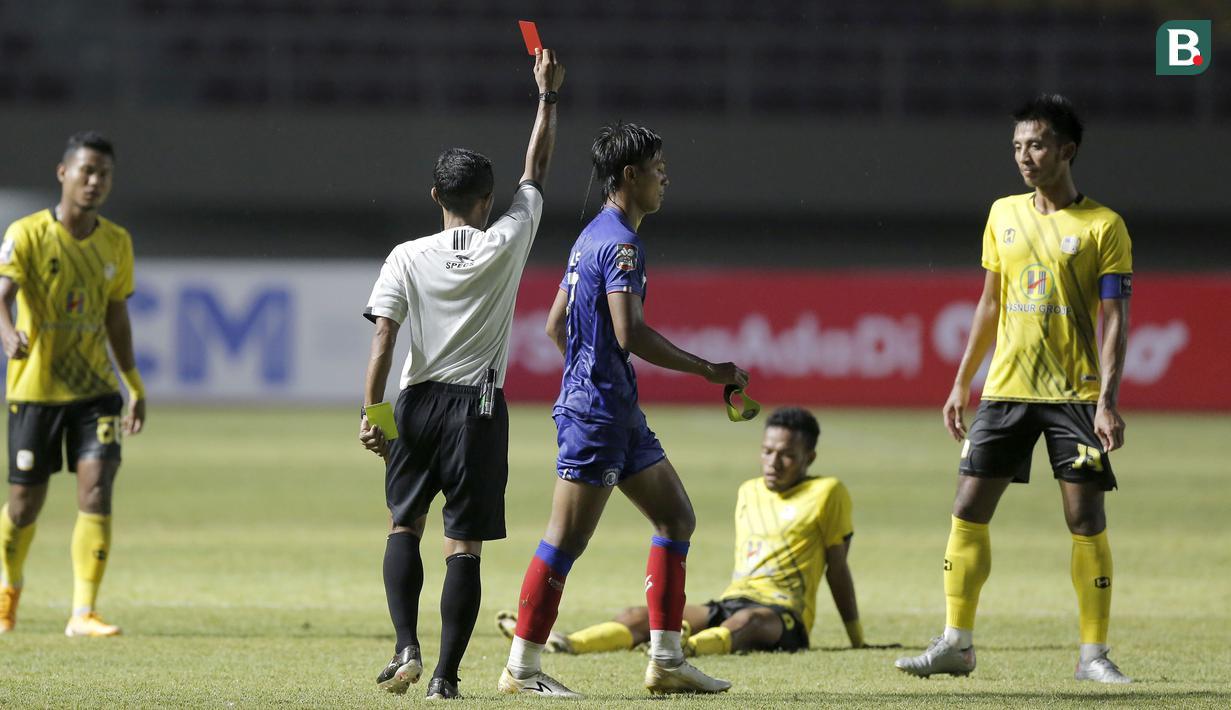 Bek Arema FC, Johan Ahmat Farizi (tengah) mendapat kartu merah dari wasit Mochammad Adung saat menghadapi Barito Putera dalam laga matchday ke-2 Grup A Piala Menpora 2021 di Stadion Manahan, Solo, Kamis (25/3/2021). Arema FC kalah 1-2 dari Barito Putera. (Bola.com/Arief Bagus)