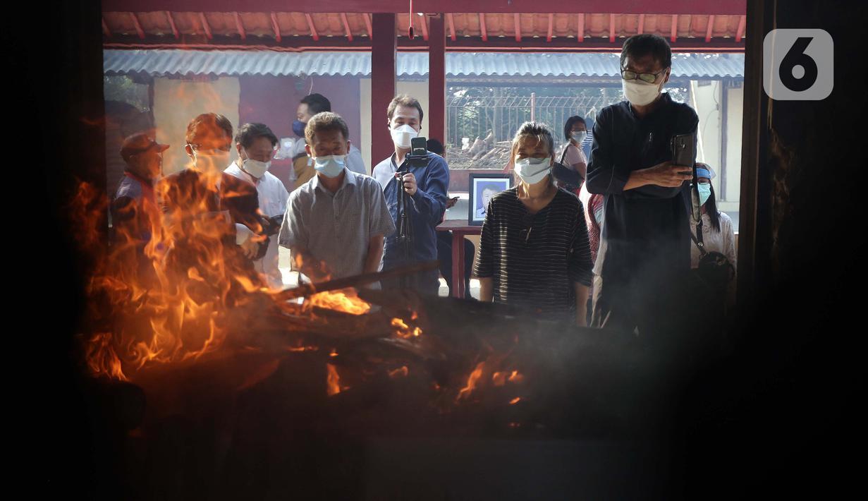 Keluarga dan kerabat menyaksikan proses kremasi jenazah di Krematorium Cilincing, Jakarta, Kamis (29/7/2021). Sejak 19 Juli 2021, Krematorium Cilincing juga melayani kremasi jenazah dengan protokol COVID-19. (Liputan6.com/Helmi Fithriansyah)
