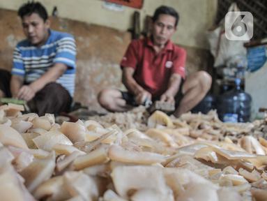 Pekerja menyelesaikan pembuatan kerupuk kulit di industri rumahan kawasan Bogor, Jawa Barat, Minggu (26/9/2021). Pelaku usaha kerupuk kulit mengaku permintaan kerupuk kulit mengalami penurunan hingga 50 persen akibat Pemberlakuan Pembatasan Kegiatan Masyarakat (PPKM). (merdeka.com/Iqbal S Nugroho)