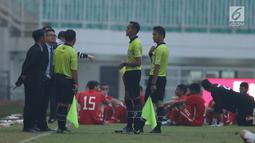 Wasit Mustafa Umarella (kedua kanan) berbincang dengan pengawas pertandingan saat laga Bahrain melawan Korea Utara dihentikan akibat lampu mati pada  PSSI Anniversary Cup 2018 di Stadion Pakansari, Kab Bogor, Kamis (3/5). (Liputan6.com/Helmi Fithriansyah)