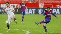 Penyerang Barcelona, Lionel Messi menembak bola saat bertanding melawan Sevilla pada pertandingan leg pertama semifinal Copa del Rey di stadion Ramon Sanchez Pizjuan, Spanyol, Kamis (10/2/2021).  Laga semifinal leg kedua bakal digelar 27 Februari mendatang di Camp Nou. (AP Photo/Angel Fernandez)