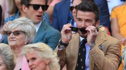 Mantan pesepak bola Inggris, David Beckham menyaksikan babak semifinal Grand Slam Wimbledon di All England Lawn Tennis Club, Kamis (11/7/2019). David Beckham menjadi saksi petenis Rumania Simona Halep lolos ke final usai menang atas Elina Svitolina dari Ukraina 6-1, 6-3. (Mike Egerton/POOL/AFP)
