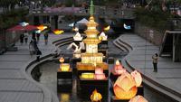 Pengunjung yang mengenakan masker wajah sebagai tindakan pencegahan penyebaran virus corona COVID-19 berjalan dekat lentera yang dipajang untuk perayaan ulang tahun Buddha pada 19 Mei mendatang di Seoul, Korea Selatan, Senin (10/5/2021). (AP Photo/Lee Jin-man)