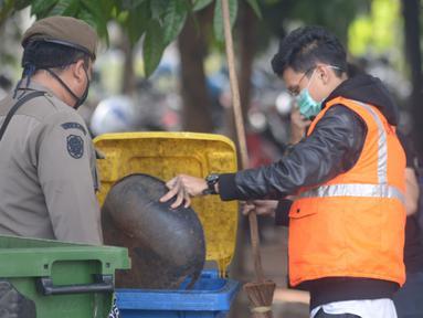 Seorang pelanggar dihukum membersihkan sampah saat Operasi Yustisi Protokol COVID-19 di Kawasan Bundaran HI, Jakarta, Selasa (15/9/2020). Operasi Yustisi itu untuk menegakkan pemakaian masker guna menekan perilaku warga yang memicu angka kenaikan infeksi Covid-19. (merdeka.com/Imam Buhori)