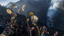 Warga berebut uang dan hasil bumi yang dilemparkan anggota suku Tengger selama Festival Yadnya Kasada di Probolinggo, Jawa Timur (10/7). Warga Tengger melakukan ritual lempar hasil bumi sebagai wujud syukur pada Sang Hyang Widi. (AFP Photo/Juni Kriswanto)