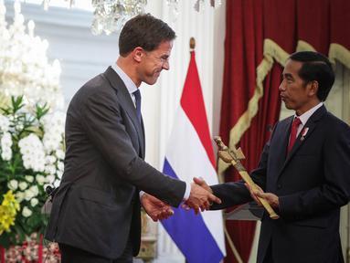 Perdana Menteri Kerajaan Belanda Mark Rutte (kiri) memberikan cindramata sebuah keris kepada Presiden Joko Widodo seusai memberikan pernyataan bersama di Istana Merdeka, Jakarta, Rabu (23/11). (Liputan6.com/Faizal Fanani)