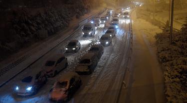 Sejumlah mobil terjebak salju tebal yang menyelimuti Jalan Lingkar M30 di Madrid, Spanyol, Jumat (8/1/2021). Ribuan mobil terjebak salju tebal akibat Badai Filomena yang menghantam Madrid dan sebagian besar wilayah Spanyol. (OSCAR DEL POZO/AFP)