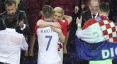 Kolinda Grabar-Kitarovic memeluk Ivan Rakitic usai laga final Piala Dunia 2018 di Luzhniki Stadium, Moskow, Rusia, (15/7/2018). Meski Kroasia kalah Kolinda tetap tersenyum manis. (AP/Thanassis Stavrakis)