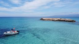 Sebuah perahu terlihat dari pemandangan udara di Akamas di sepanjang pantai barat Siprus (31/5/2020). Semenanjung ini dinamai setelah putra Theseus, pahlawan Perang Troya dan pendiri kerajaan kota Soli. (AFP Photo/Etienne Torbey)