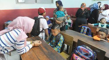 Seorang ibu menenangkan anaknya yang merajuk saat hari pertama masuk sekolah di SDN Cinere 1, Depok, Jawa Barat, Senin (15/7/2019). Seluruh siswa SD, SMP dan SMA, pada hari ini mulai masuk sekolah pada tahun ajaran baru 2019/2020. (merdeka.com/Arie Basuki)
