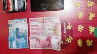 Sejumlah barang bukti berupa ratusan pil keras, handphone dan uang yang berhasil diamankan aparat kepolisian.