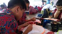 Para pelajar Cirebon semangat membatik motif Mega Mendung demi memecahkan rekor Muri dan dunia. Foto (Liputan6.com / Panji Prayitno)