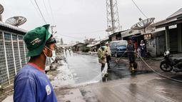 Petugas membersihkan jalanan yang tertutup abu vulkanik Gunung Sinabung di Karo, Sumatra Utara (19/2). Gunung Sinabung kembali aktif pada tahun 2010 untuk pertama kalinya sejak 400 tahun terakhir. (AFP Photo/Ivan Damanik)